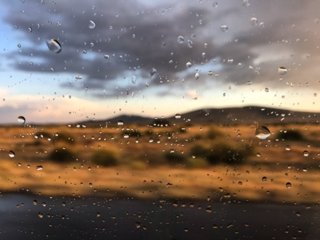 Roadside desert at sunset shown through a window with raindrops