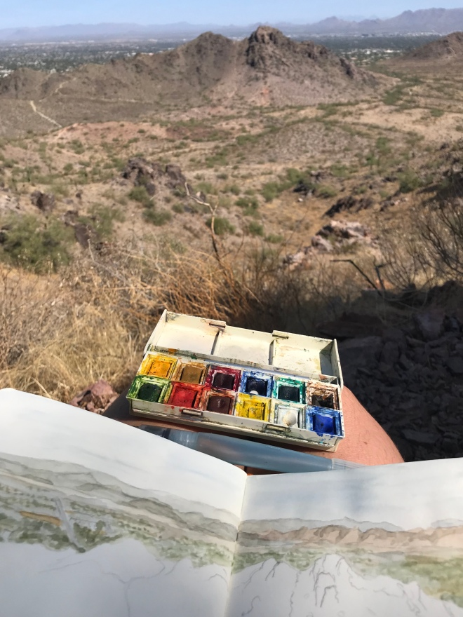 Photo of sketchbook and watercolors with desert valley in the background